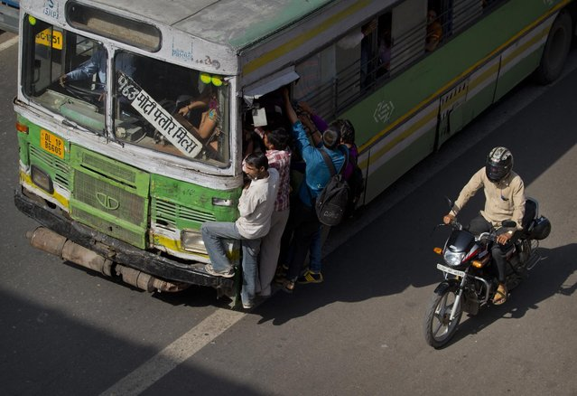 Commuters hang on the door of a crowded bus in New Delhi, India, Friday, April 10, 2015. Carrying more than stipulated capacity puts pressure on the engines of motor vehicles resulting in more pollution. According to the World Health Organization, air pollution kills millions of people every year, including more than 627,000 in India. (Photo by Saurabh Das/AP Photo)