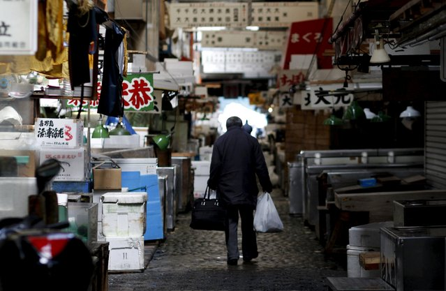 A man walks after shopping at the Tsukiji fish market in Tokyo in this March 19, 2011 file photo.  Japan is expected to report inflation data this week. (Photo by Toru Hanai/Reuters)