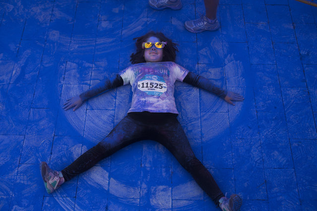 A child plays on the floor covered with clouded power, at the end of a mini marathon during a Holi Run Festival in Madrid, Spain, Sunday, April 12, 2015. (Photo by Andres Kudacki/AP Photo)