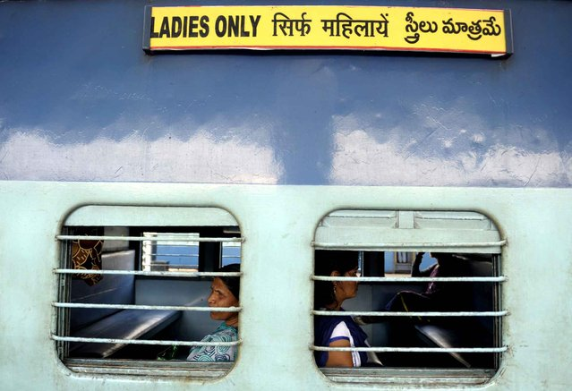 """Indian passengers sit in a """"Ladies Only"""" carriage as they wait for a train to depart from a platform at Secunderabad Railway Station in Hyderabad on February 25, 2016, as Indian Railways Minister Suresh Prabhu presents The Railway Budget at Parliament House in New Delhi. (Photo by Noah Seelam/AFP Photo)"""