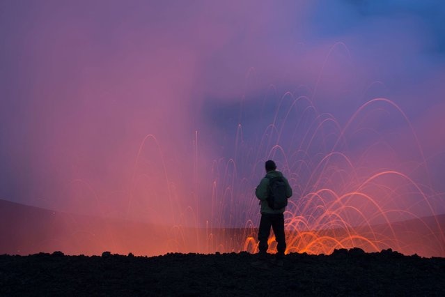 A tourist stands on the edge of the fountain of lava. (Photo by Denis Budkov/Caters News)