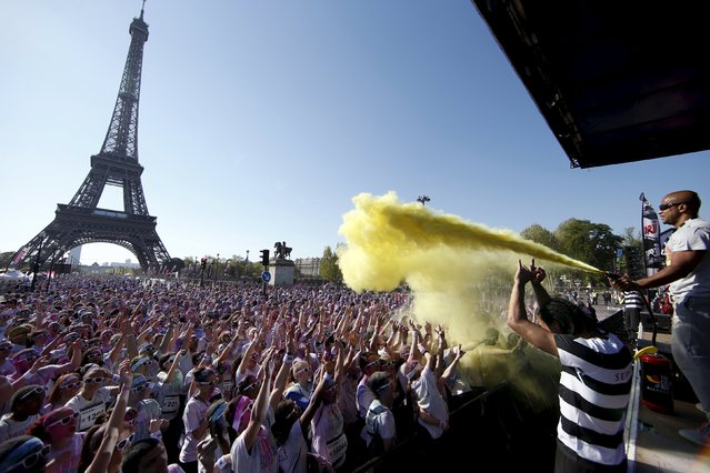 Participants take part in the Color Run near the Eiffel Tower in Paris April 19, 2015. The Color Run is a five-kilometre race, held in cities across the U.S. and also worldwide, with the aim of promoting healthy living and to benefit a charity that organizers choose in each of the cities that the run visits. Participants are doused from head to toe in different colors at each kilometre. (Photo by Benoit Tessier/Reuters)