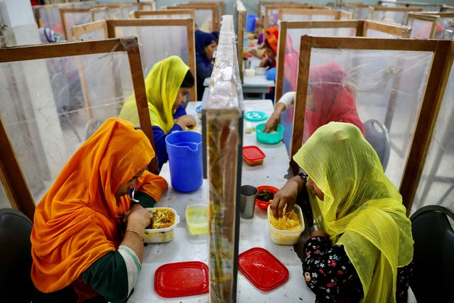 Employees dine between polythene sheets, as a safety measure to reduce the spread of coronavirus disease (COVID-19), at The Civil Engineering Limited garment factory in Dhaka, Bangladesh, August 17, 2021. (Photo by Mohammad Ponir Hossain/Reuters)
