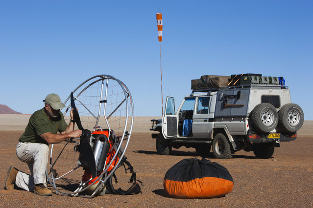 Theo Allofs taking his paraglider engine apart after flight over the desert, in October, 2014, in the Namib Desert, Namibia. A photographer has captured a bird's eye view of the stunning Namib Desert from a paraglider. Theo Allofs travels the world taking stunning pictures of untouched landscapes from a unique perspective. (Photo by Theo Allofs/Barcroft Media)