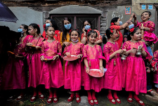 Group of young girls with their parents wait to worship Lord Narsimha during Narsimha festival in Lalitpur, Nepal, 27 August 2021. The Lord Narsimha is worshipped as protector of Natural disasters. Hundreds of devotees of ethnic Newar community of Patan city celebrated the Narsimha festival in the hope of a world peace, prosperity and prevention from the natural disasters for the upcoming year. The Narsimha festival is believed to be started on the 17th Century. (Photo by Narendra Shrestha/EPA/EFE)