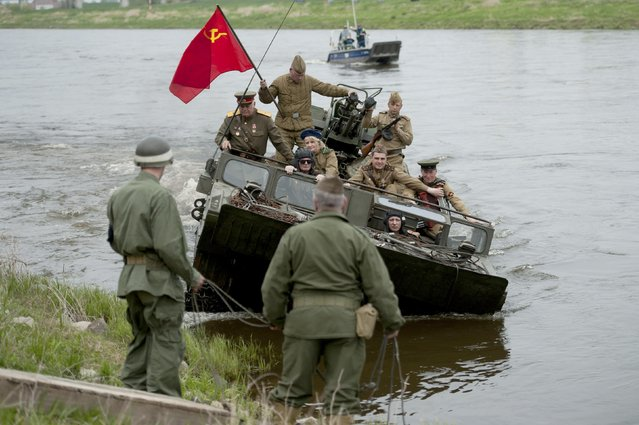 Members of a historical re-enactment group dressed as U.S. and Soviet Army soldiers take part in Elbe Day celebrations, in eastern German city of Torgau at the river Elbe, April 25, 2015. Elbe Day commemorates the encounter of the Allies 70 years ago, on the 25th of April 1945 when American and Soviet army units joined together on the destroyed bridge over the river Elbe. (Photo by Stefanie Loos/Reuters)