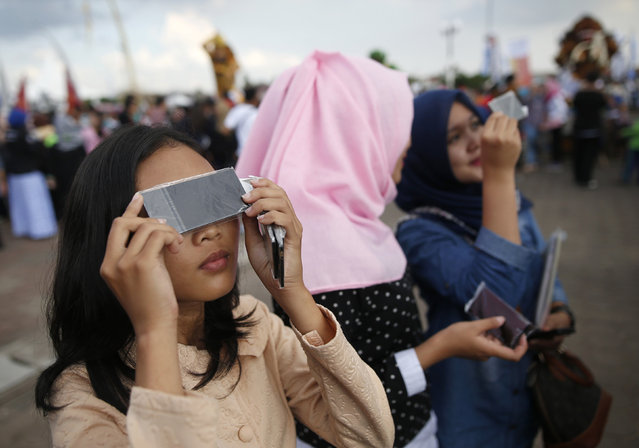 People test filters for watching a solar eclipse near the Ampera Bridge on the Musi River the day before thousands of people are expected to gather to witness the event in Palembang, South Sumatra province, Indonesia March 8, 2016. (Photo by Darren Whiteside/Reuters)