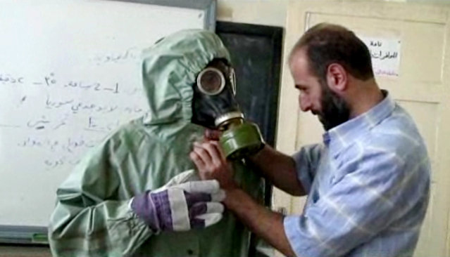 This image made from an AP video posted on Wednesday, September 18, 2013 shows a volunteer adjusting a students gas mask and protective suit during a session on reacting to a chemical weapons attack, in Aleppo, Syria. (Photo by AP Photo via AP video)