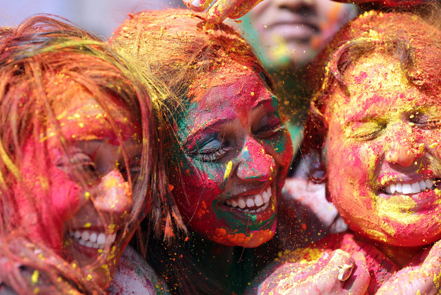 Women play with powdered colors as they take part in Holi festival celebrations at Durgiana Temple in Amritsar, India, 20 March 2019. Holi is observed at the end of the winter season on the last full moon day of the lunar month Phalguna, which usually falls in the later part of February or March and is celebrated by people throwing colored powder and colored water at each other. (Photo by Raminder Pal Singh/EPA/EFE)