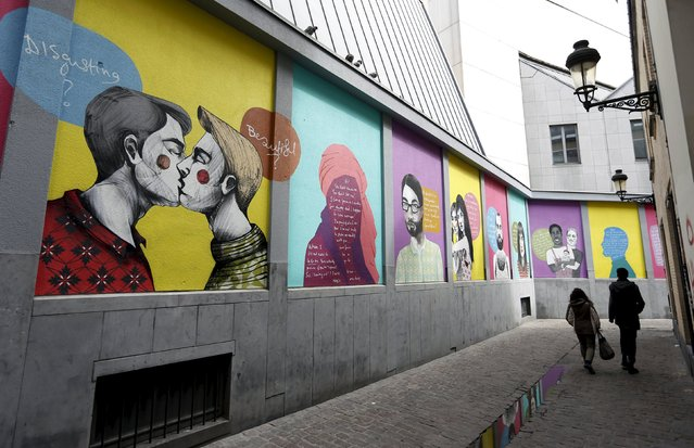"A couple walks past artworks of Greek artist Fotini Tikkou ""Out in the Street"", part of a giant fresco promoting lesbian, gay, bisexual and transgender (LGBT) street art and aiming to fight against homophobia and sexual discriminations in central Brussels, Belgium, May 1, 2015. (Photo by Francois Lenoir/Reuters)"