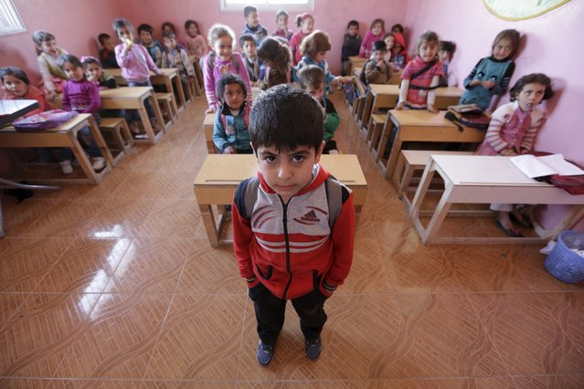 Five-year-old Yousef Madr al-Ajaj poses inside a classroom in the rebel-controlled area of Maarshureen village in Idlib province, Syria March 12, 2016. (Photo by Khalil Ashawi/Reuters)