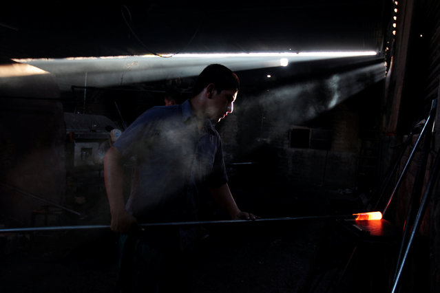 A glassmaker works next to a furnace at Cespedes factory in Olocuilta, El Salvador February 8, 2017. (Photo by Jose Cabezas/Reuters)