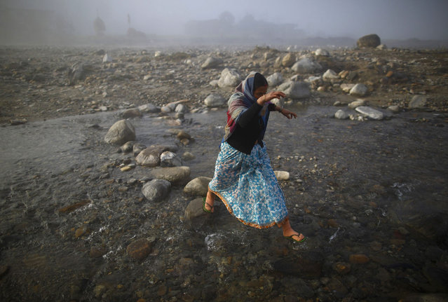 A women jump to reach a rock as she crosses Chepay River at Sapay, Achham in the Far-Western region of Nepal, around 900 km (559 miles) from Kathmandu February 17, 2014. (Photo by Navesh Chitrakar/Reuters)