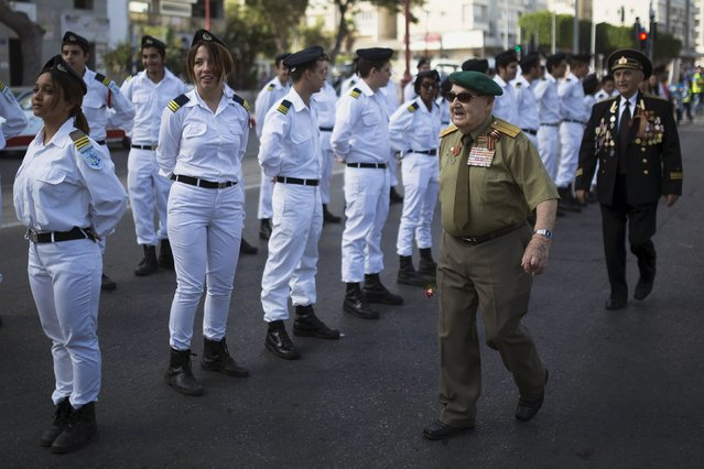 World War Two veterans walk past Israeli naval officers during a parade marking the upcoming Victory Day, the anniversary of the Allied victory over Nazi Germany, in the southern city of Ashdod, Israel, May 8, 2015. (Photo by Amir Cohen/Reuters)