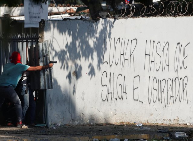 "A demonstrator aims a pistol next to a graffiti reading ""Fight until the usurper leaves"" during clashes with security forces following a rally against the government of Venezuela's President Nicolas Maduro and to commemorate May Day in Caracas, Venezuela, May 1, 2019. (Photo by Carlos Garcia Rawlin/Reuters)"