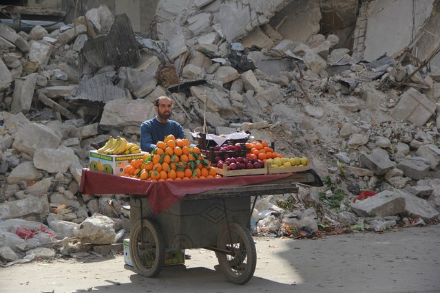 A Syrian fruit vendor waits for customers next to a damaged building on February 24, 2014 in the Shaar neighborhood of the northern city of Aleppo. (Photo by Mohammed Al-Khatieb/AFP Photo)
