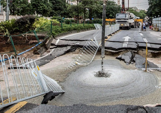 A road is being repaired after it collapsed in a heavy rain, in Guangzhou, Guangdong province, China, May 4, 2015. (Photo by Reuters/Stringer)