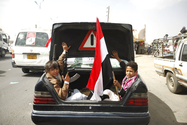 Houthi followers sit on the back of car with Yemen's national flag before they attend a rally marking one year of Saudi-led air strikes, in Yemen's capital Sanaa, March 26, 2016. (Photo by Mohamed al-Sayaghi/Reuters)