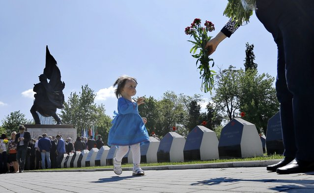A Russian girl rushes toward her grandmother, to take some flowers to be laid on the nearby thumbs,  during a commemoration ceremony for the Russian soldiers that were killed 70 years ago during WWII, in Bucharest, Romania, 08 May 2015. (Photo by Robert Ghement/EPA)