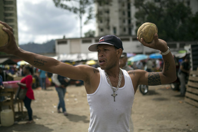 A vendor hawks melons at the Coche Market in Caracas, Venezuela, Thursday, May 2, 2019. The bustling open-air market in Caracas came back to life after violent unrest shook Venezuela amid a power struggle that left at least four dead. (Photo by Rodrigo Abd/AP Photo)