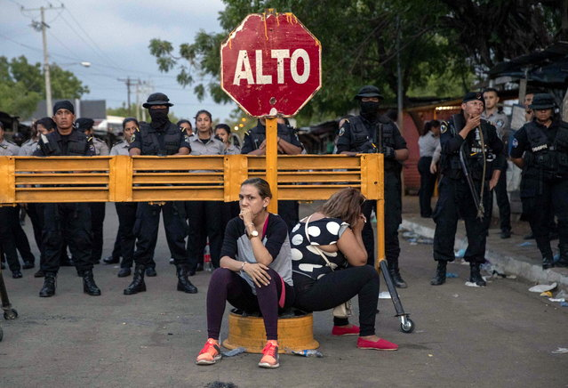 """Relatives of """"political prisoners"""" sit in front of riot police during a protest to demand information about detainees, outside the """"La Modelo"""" prison, near Managua, Nicaragua, 16 MAy 2019. At least one person has died after a riot broke out on 16 May. (Photo by Jorge Torres/EPA/EFE)"""