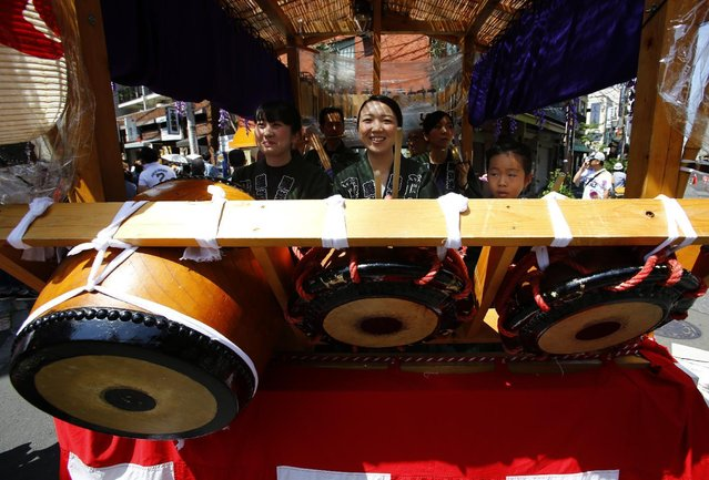 Women wearing traditional happi coats perform a drum on board a float as it is paraded during an annual Sanja Festival at Tokyo's Asakusa shopping district Sunday, May 17, 2015. Japan's Sanja Festival is one of three big festivals in Tokyo and is held on the third weekend of May. (Photo by Shizuo Kambayashi/AP Photo)