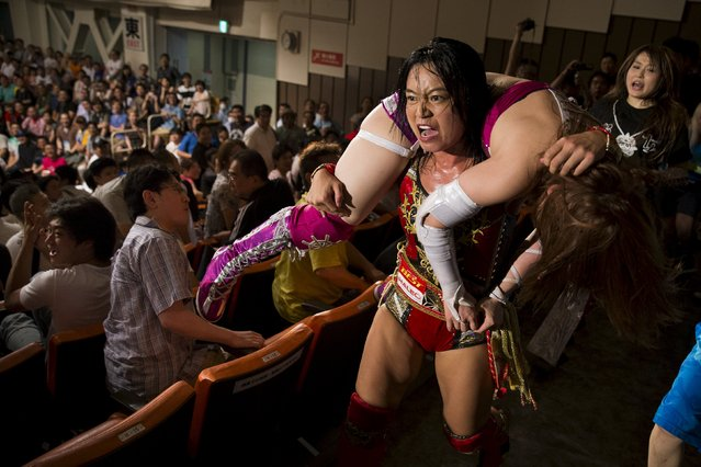 Wrestler Mieko Satomura carries her opponent  Kairi Hojo through the audience area during a Stardom female professional wrestling show at Korakuen Hall in Tokyo, Japan, July 26, 2015. (Photo by Thomas Peter/Reuters)