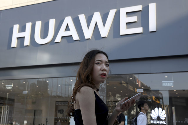 A woman uses a smartphone outside a Huawei store in Beijing Monday, May 20, 2019. Google is assuring users of Huawei smartphones the American company's services still will work on them following U.S. government restrictions on doing business with the Chinese tech giant. (Photo by Ng Han Guan/AP Photo)