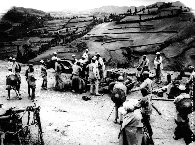1939: Chinese soldiers and labourers carry parts of an American leased Jeep over mountain trails for re-assembly on the repaired section of the Burma Road in China