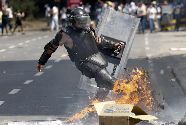 A riot police officer kicks a burning barricade during clashes with anti-government protesters in Caracas March 20, 2014. Venezuelan intelligence agents on Wednesday arrested one opposition mayor accused of stoking violent protests, while another was jailed for 10 months in the latest moves against rivals of Venezuela's President Nicolas Maduro. (Photo by Christian Veron/Reuters)