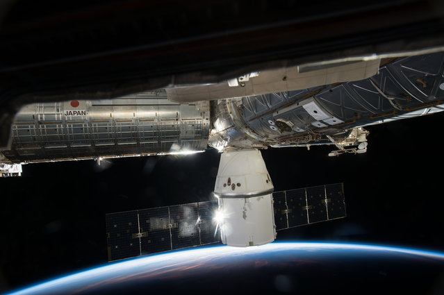SpaceX's Dragon cargo capsule is seen docked to the Earth facing port of the International Space Stations's Harmony module. SpaceX's sixth commercial resupply flight to the ISS launched on April 14 and arrived three days later. It will depart with over 3,100 pounds of research samples and equipment and splashdown in the Pacific Ocean on May 21, 2015. (Photo by NASA)