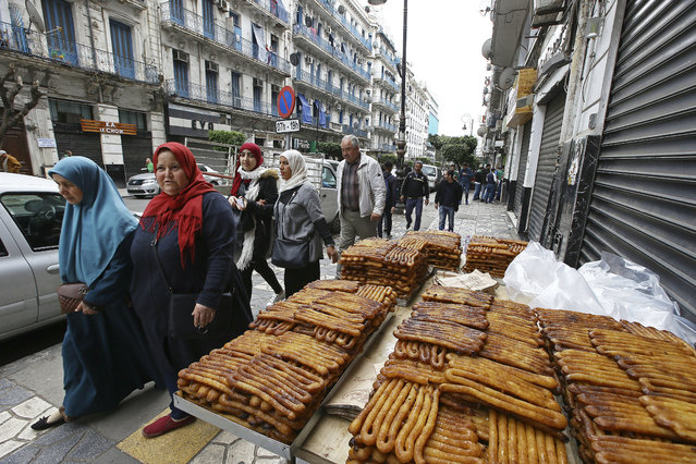 Women pass a roadside pastry stand when heading to a demonstration in Algiers, Friday April 5, 2019. (Photo by Sidali Djarboub/AP Photo)