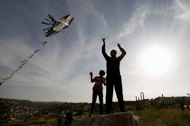 A man and his son fly a kite during an event celebrating spring at the Citadel in Amman, Jordan, April 15, 2016. (Photo by Muhammad Hamed/Reuters)