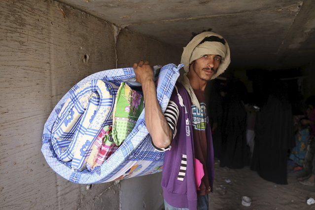 A man carries his luggage as he leaves an underground water tunnel with other displaced people after they were forced to flee their home due to ongoing air-strikes carried out by the Saudi-led coalition in Sanaa May 2, 2015. (Photo by Mohamed al-Sayaghi/Reuters)