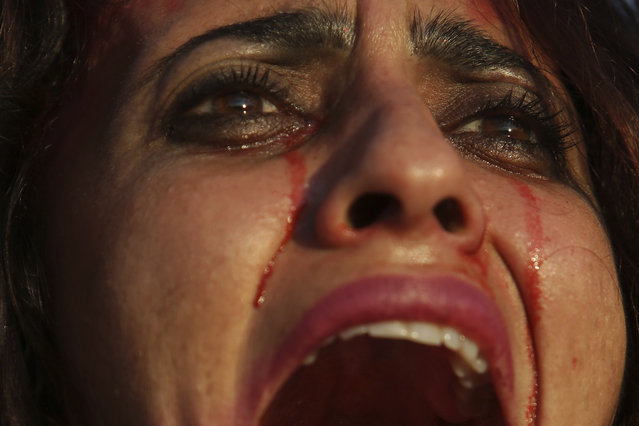 A woman covered in fake blood shouts slogans defending a women's right to have an abortion during protest marking International Women's Day in Brasilia, Brazil, Wednesday, March 8, 2017. (Photo by Eraldo Peres/AP Photo)
