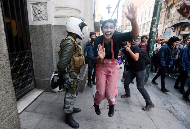 A student painted as a clown performs next to a police officer during a demonstration to demand changes in the education system in Valparaiso, Chile, April 21, 2016. (Photo by Rodrigo Garrido/Reuters)