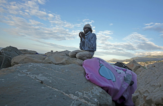 A migrant prays at sunrise on the rocks of the seawall at the Saint Ludovic border crossing on the Mediterranean Sea between Vintimille, Italy and Menton, France, June 17, 2015. Police on Tuesday began hauling away mostly African migrants from makeshift camps on the Italy-France border as European Union ministers met in Luxembourg to hash out plans to deal with the immigration crisis.  REUTERS/Eric Gaillard
