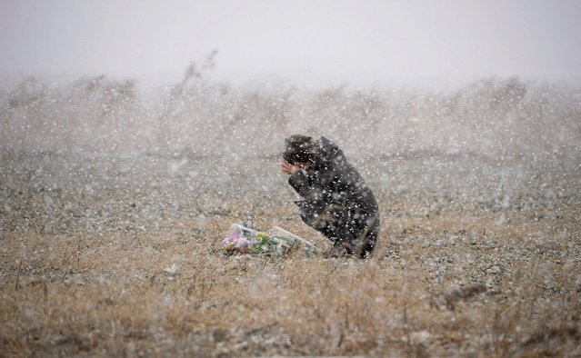 A woman prays for the deceased as snow falls, at a place where she was employed at a photo studio at the time, in Rikuzentakata, Iwate prefecture, March 11, 2014. (Photo by Reuters/Kyodo News)