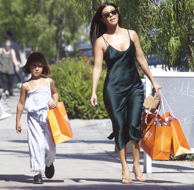 Kourtney Kardashian turns heads in a silk midi dress as she takes her daughter Penelope shopping in Los Angeles on July 13, 2019. (Photo by The Mega Agency)