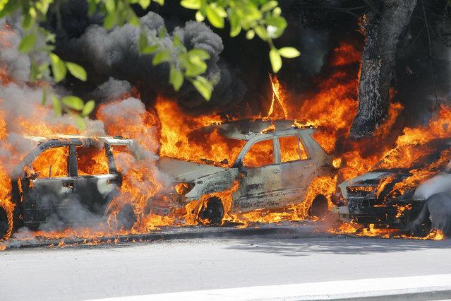 Cars burn after a poweful car bomb in Mogadishu, Somalia, Wednesday, April 17, 2019. (Photo by Farah Abdi Warsameh/AP Photo)