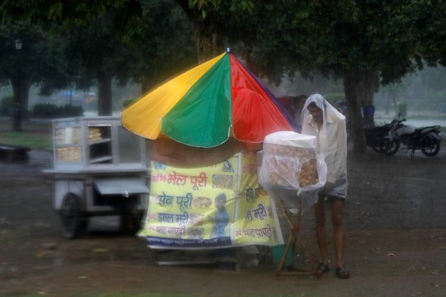 A vendor selling snacks covers himself with a plastic sheet as it rains in New Delhi, India, July 15, 2019. (Photo by Anushree Fadnavis/Reuters)