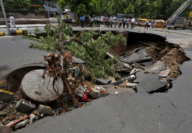 Onlookers stand next to a road that was damaged after heavy rains in Ahmedabad, India, June 25, 2015. (Photo by Amit Dave/Reuters)