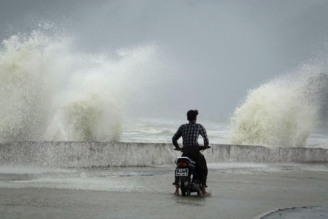 A man rides a motorbike along a coastal road as strong winds and waves batter the shoreline at Sittwe beach during monsoon season in Sittwe, Rakhine state, Myanmar, 06 July 2019. (Photo by Nyunt Win/EPA/EFE)