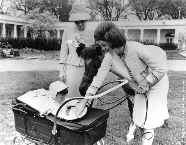 American first lady, Jackie Kennedy (1929 - 1994) (wife of US President John F. Kennedy), introduces her son, John Kennedy Jr. (1960 - 1999) to Farah, Empress Of Persia in the grounds of the White House, 1962