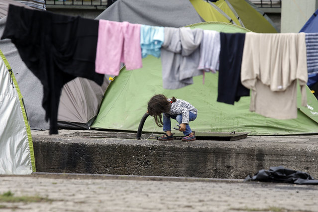 A child drinks water  from a pipe on the platform of a trim station which was turned into a makeshift camp crowded by migrants and refugees at the northern Greek border point of Idomeni, Greece, Monday, May 2, 2016. Many thousands of migrants remain at the Greek border with Macedonia, hoping that the border crossing will reopen, allowing them to move north into central Europe. (Photo by Gregorio Borgia/AP Photo)