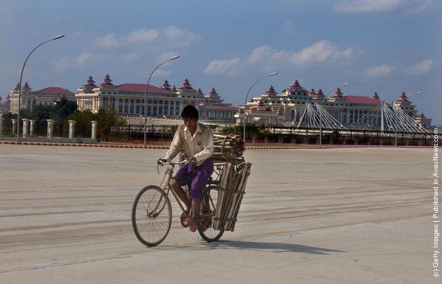 A Burmese man cycles past the massive parliament complex