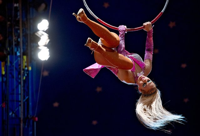 A high-flying circus performer swings on her ring above the center stage at the Cole Brothers Circus at the Rockingham County Fairgrounds in Harrisonburg, Va., on April 23, 2014. (Photo by Jason Lenhart/Daily News-Record via AP Photo)