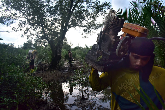 A local artisanal miner carrying an air compressor used for mining under the mud on March 22, 2017 in Paracale, Philippines. Apart from tunneling and sifting sand, locals dive down murky swamps with the aid of a compressor with air flowing in a small tube for breathing, as they blindly swim under the mud for up to four hours to look for tiny rocks containing gold particles. For decades, local residents at Paracale town work in hazardous conditions scavenging under the earth and diving into tunnels filled with mud using only makeshift tools to mine for gold, often placing their health and lives at risk. (Photo by Jes Aznar/Getty Images)