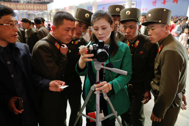 Soldiers check their souvenir photo as they visit the flower exhibition marking the 105th birth anniversary of the country's founding father, Kim Il Sung in Pyongyang, North Korea April 16, 2017. (Photo by Damir Sagolj/Reuters)