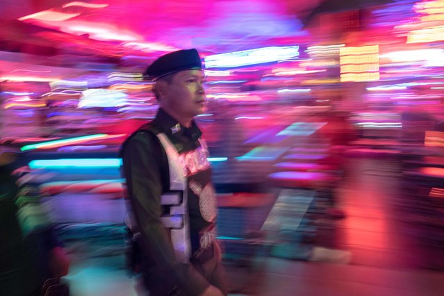 This photo taken on March 29, 2017 shows a Thai policeman patrolling Walking Street in Pattaya. (Photo by Roberto Schmidt/AFP Photo)